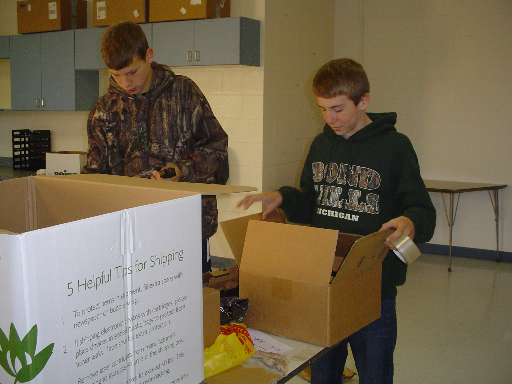 Two Ontonagon students sorting through recyclables and preparing them for shipping