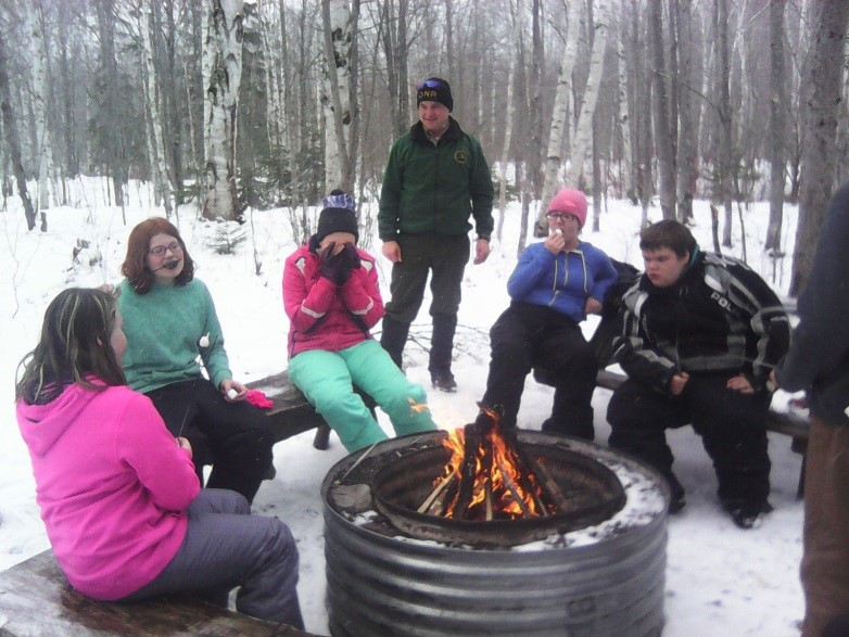 Junior High Students are gathered around a fire in the woods